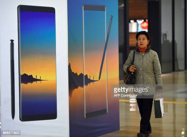 A woman walks past an advertisement for the Samsung Galaxy Note8 at the company's showroom in Seoul on October 31 2017 South Korean tech giant...