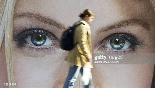 A woman walks past an advertising billboard for cosmetics featuring a closeup of a pair of women's eyes in Berlin on May 4 2011 AFP PHOTO / JOHN...
