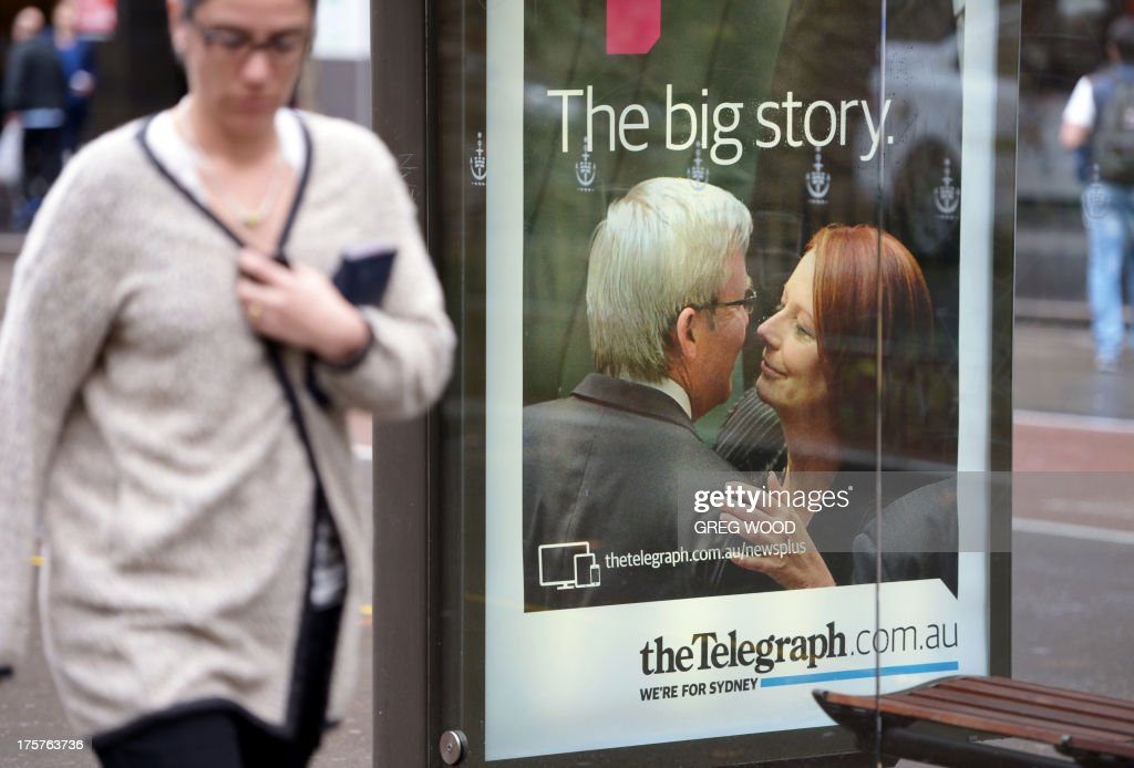 A woman walks past an advertising board for media tycoon Rupert Murdoch's key tabloid the Sydney Daily Telegraph at a bus shelter in Sydney on August...