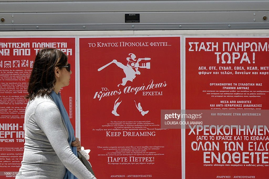 A woman walks past an anarchist anti-police and anti-media poster in Athens during a general strike demonstration against the government's draconian austerity cuts on May 20, 2010 in Athens. 'The social state is on its way out, the security state is coming in,' ' Keep dreaming' the poster reads.Thousands of protesters took to the streets of Athens and second city Thessaloniki on Thursday in a new general strike against the government's debt-dictated austerity spending cuts and pension reform. AFP PHOTO / Louisa Gouliamaki