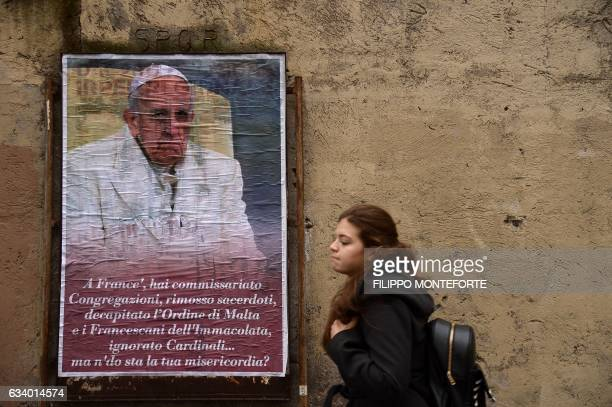 A woman walks past an antiPope Francis poster with a portrait of the Pope and a message reading 'Francis you under receivership congregations removed...
