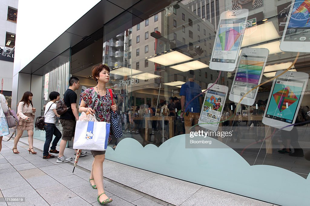 A woman walks past an Apple Inc. store in the Ginza district of Tokyo, Japan, on Sunday, June 23, 2013. Samsung and Apple, the worlds two biggest smartphone makers, have each scored victories in patent disputes fought over four continents since the maker of the iPhone accused Asias biggest electronics maker of slavishly copying its devices. Photographer: Koichi Kamoshida/Bloomberg via Getty Images