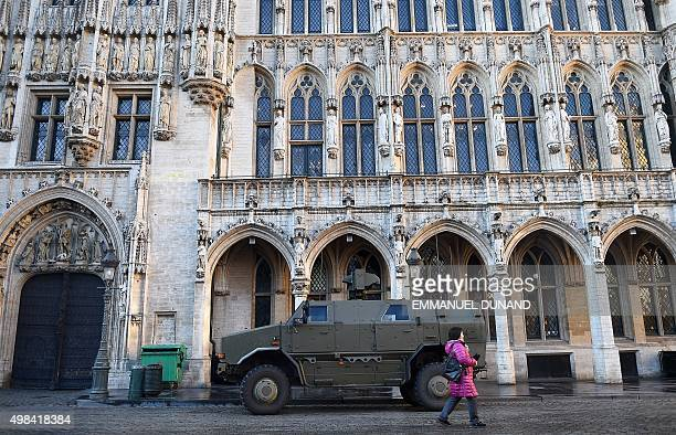 A woman walks past an armoured personnel carrier at Grand Place central square in Brussels on November 23 2015 as the Belgian capital remains on the...