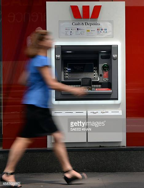 A woman walks past an ATM machine of Australian banking giant Westpac in the central business district of Sydney on November 3 2014 Westpac posted a...