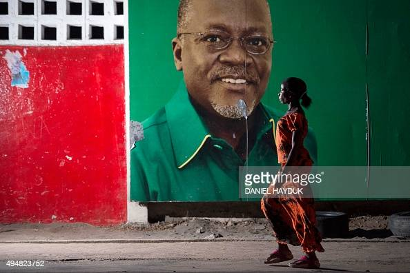 A woman walks past an election billboard after ruling party Chama Cha Mapinduzi candidate John Magufuli was named presidentelect by the National...