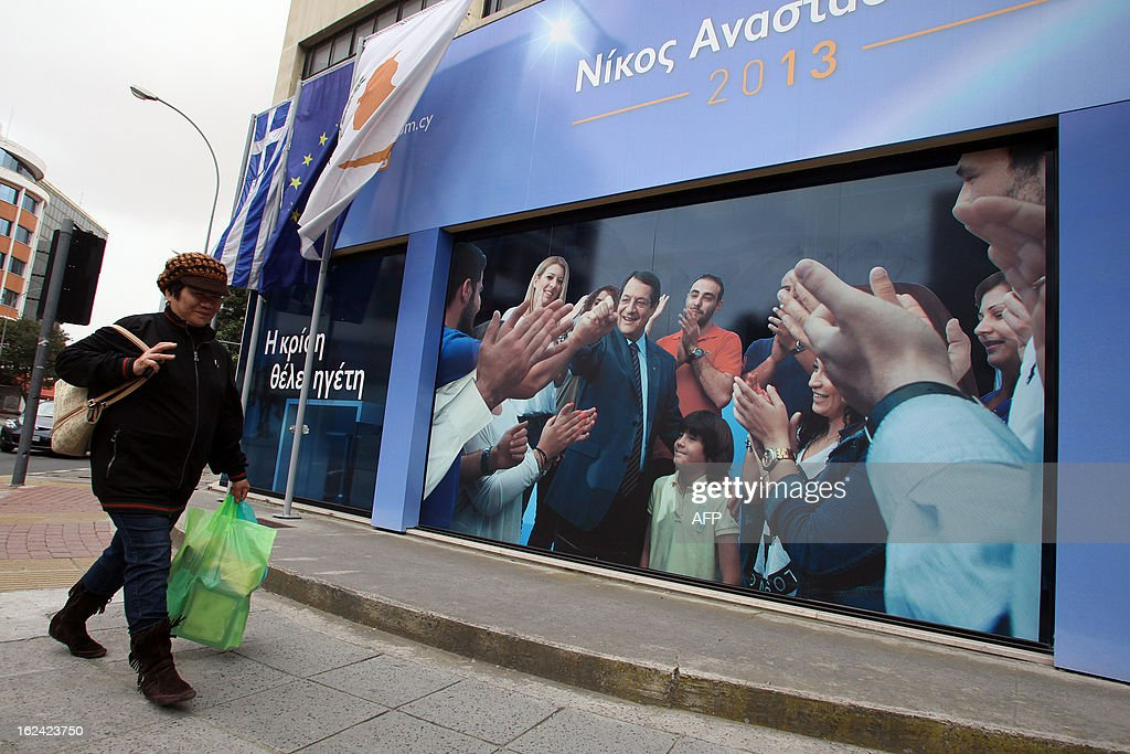 A woman walks past an election poster for Cyprus' right-wing presidential candidate Nicos Anastasiades one day before the second run-off of the Cypriot presidential elections in Nicosia, on February 23, 2013. A second-round runoff on February 24, being closely watched in European capitals pits opposition leader Anastasiades against Stavros Malas, who is backed by the communist party in power during the economic downturn, Akel.