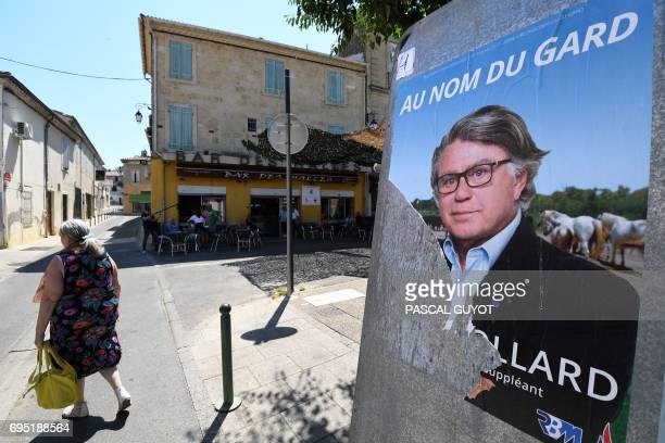 A woman walks past an election poster of Gilbert Collard France's farright National Front party candidate for the legislative elections in the second...