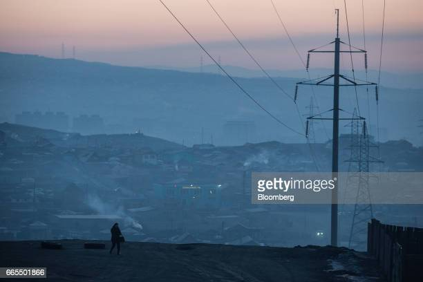 A woman walks past an electricity pylon towards a bus stop as smoke rises over a ger district in Ulaanbaatar Mongolia on Tuesday March 14 2017 The...