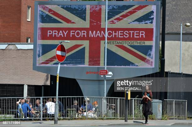 TOPSHOT A woman walks past an electronic advertising board displaying a Union flag and the words 'Pray For Manchester' close to the Manchester Arena...