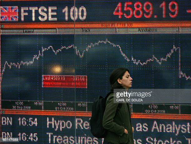 A woman walks past an electronic sign showing the progress of the FTSE 100 share index in London on October 6 2008 The London stock market nosedived...