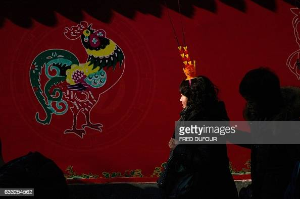 A woman walks past an image of a rooster at a temple fair in Ditan park during Lunar New Year celebrations in Beijing on February 1 2017 The Lunar...