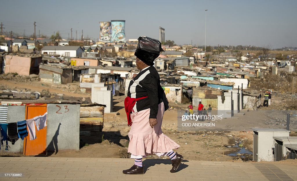 A woman walks past an informal settlement in the Soweto neighbourhood of Orlando on June 28 2013 US President Barack Obama will visit the township...