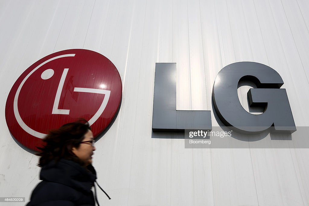 A woman walks past an LG Electronics Inc. logo in Seoul, South Korea, on Wednesday, Jan. 22, 2014. LG Electronics, the worlds second-largest seller of televisions, is scheduled to announce fourth-quarter earnings on Jan. 27. Photographer: SeongJoon Cho/Bloomberg via Getty Images