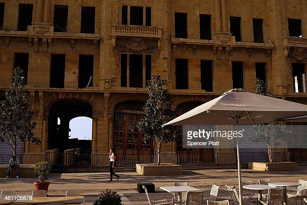 A woman walks past an old building at the start of the summer season for the Mediterranean city on June 23 2014 in downtown Beirut Lebanon While...