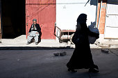 A woman walks past an old man sitting outside a storage room in the Sulaimaniyah bazaar