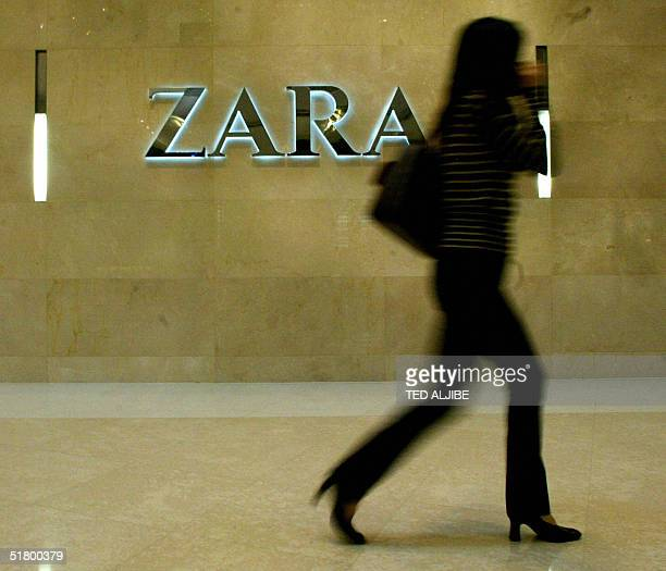 A woman walks past an outlet of the fashion chain Zara in Hong Kong 29 November 2004 Retail sales in Hong Kong a barometer of the health of the...