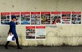A woman walks past antiterror propaganda posterspasted along the streets of Urumqi farwest China's Xinjiang region on September 16 2014 Ilham Tohti a...