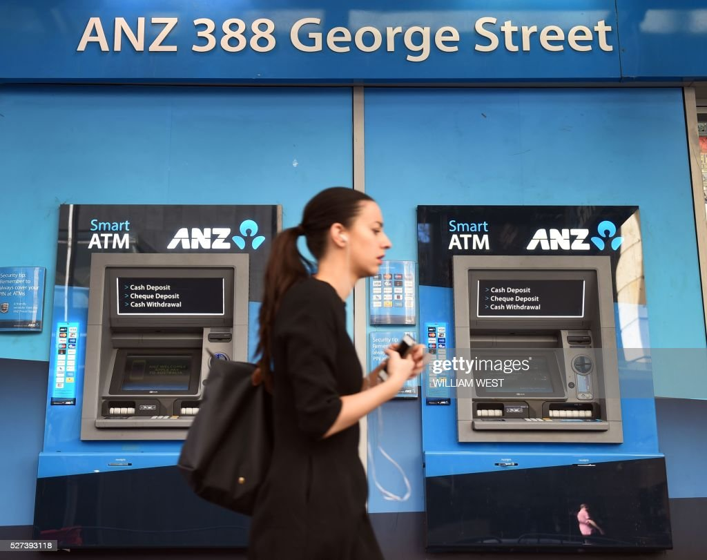 A woman walks past ANZ Bank automatic teller machines (ATMs) in Sydney on May 3, 2016. Bank on May 3 posted an interim net profit slump of 22 percent on the back of impairment and restructuring charges that the lender said would reposition it for the future. / AFP / WILLIAM