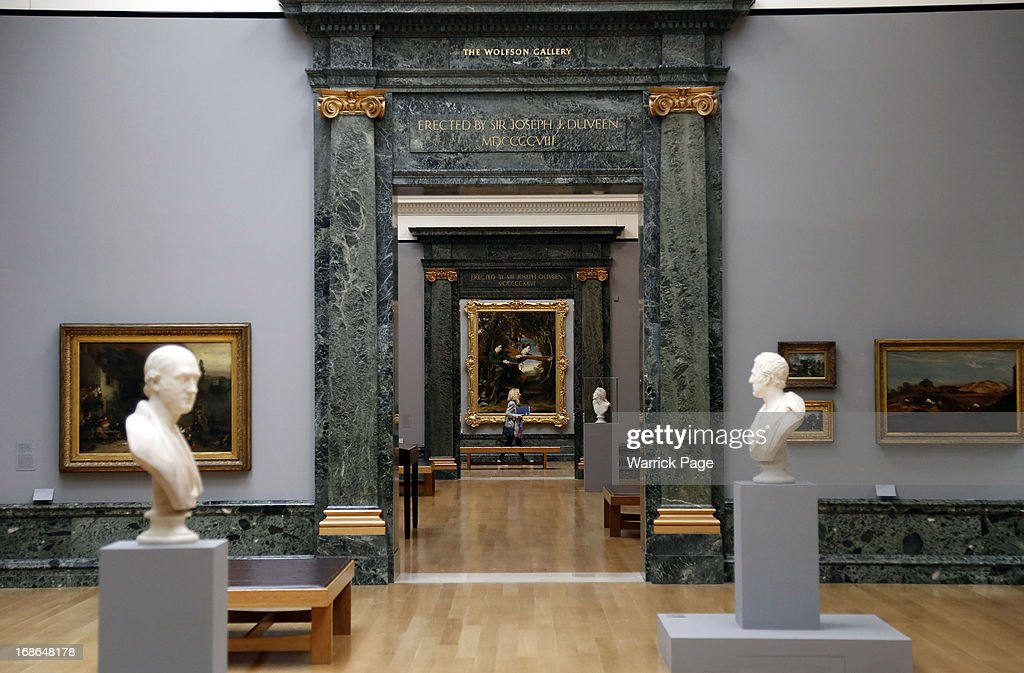 A woman walks past artwork on display at the Walk through British Art exhibition at Tate Britain on May 13, 2013 in London, England. Visitors will experience a completely new presentation of the world's greatest collection of British art, the national collection of British art will be displayed in a continuous and purely chronological display from the 1500s to the present day.