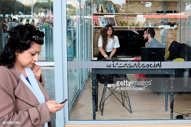 A woman walks past as Lorenzo Giustarini and Alessandra Pescara Relmi chat as they live inside a glass house at Rome's Termini station on April 27...