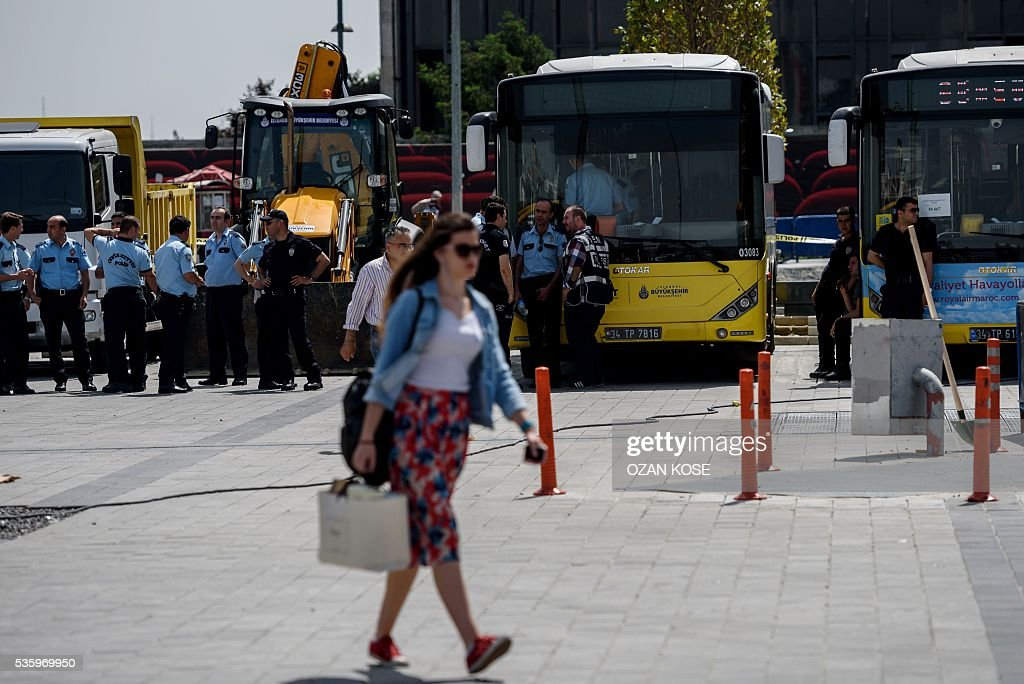 A woman walks past as Turkish anti riot police officers patrol Taksim Square in Istanbul on May 31, 2016 on the third anniversary of Gezi Park protests. The Gezi Park protests which began in May 2013, were sparked by the heavy-handed eviction of demonstrators staging a sit-in protest against the redevelopment of the area and grew into often violent clashes with police as people demonstrated against much broader issues concerning perceived infringements of civil rights . / AFP / OZAN