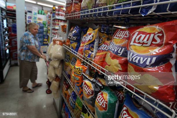 A woman walks past bags of chips manufactured by PepsiCo FritoLay brand on a shelf on March 22 2010 in Miami Florida PepsiCo announced plans to cut...