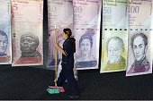 A woman walks past banners portraying the Venezuelan currency the Bolivar at the Venezuelan Central Bank in Caracas on February 10 2015 The...