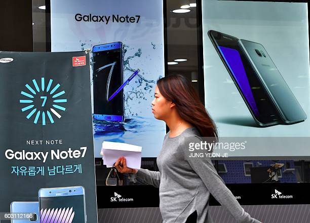 A woman walks past billboards of Samsung Galaxy Note 7 and Galaxy S7 at a mobile phone shop in Seoul on September 12 2016 Samsung shares plunged on...