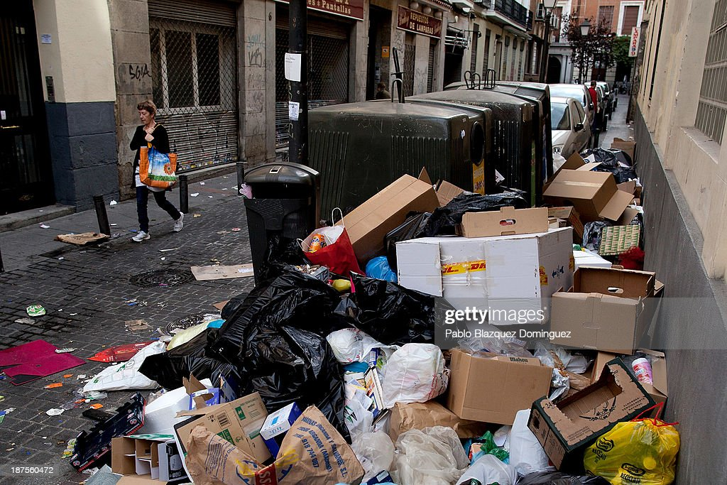 A woman walks past bins overflowing with rubbish in the city centre on November 10, 2013 in Madrid, Spain. Street cleaners, garbage collectors and public park gardeners working for Madrid city council started an indefinite strike six days ago. Franchise firms which employ them plan to axe more than 1,000 jobs and those who will remain will have to face working for a 40 percent cut in their wages.