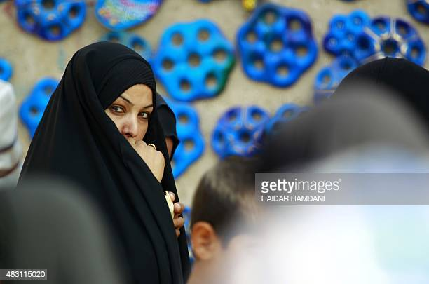 A woman walks past blue painted ceramics believed to ward off the evil eye referred to locally as the mother of seven eyes in the central Iraqi city...