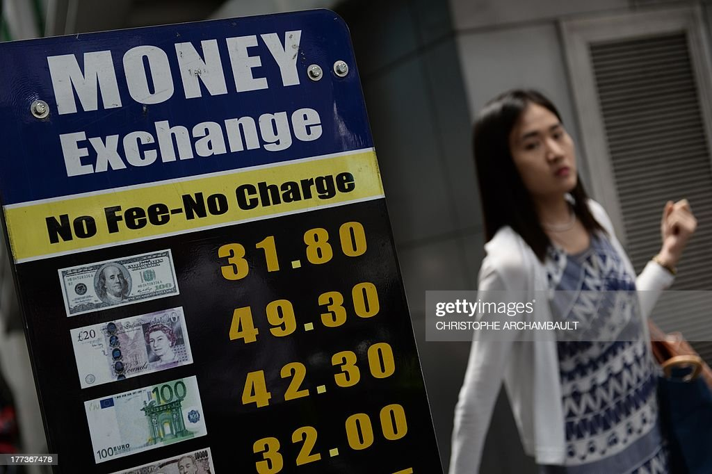 A woman walks past boards advertising currency exchange rates in downtown Bangkok on August 23, 2013. The Thai Baht fell to a three-year low of 32 against the US dollar on August 22 in line with a drop of regional currencies as economists are concerned that the US Federal Reserve will begin winding down its bond-buying scheme, which has helped fuel an investment splurge in Asia's emerging markets. AFP PHOTO / Christophe ARCHAMBAULT