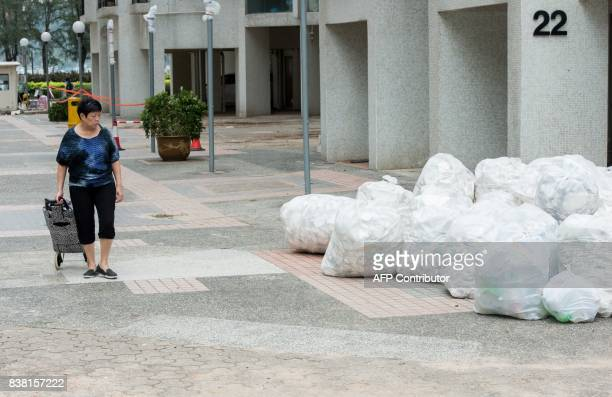 A woman walks past bundled up rubbish collected by residents and government workers in Heng Fa Chuen in Hong Kong on August 24 a day after Typhoon...