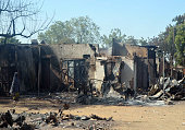 A woman walks past burnt houses after an attack by scores of Boko Haram Islamists on February 20 2014 in the northeast Nigerian town of Bama The...