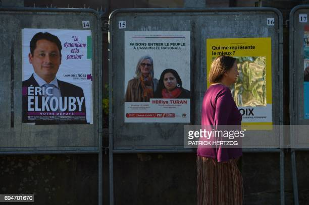 A woman walks past campaign posters outside a polling station in Strasbourg eastern France during the first round of legislative elections on June 11...