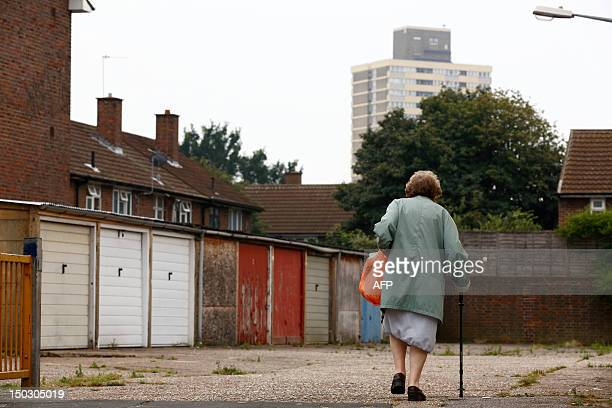 A woman walks past car garages near the High Street in Stratford east London on August 15 2012Stratford welcomed the world for the 2012 Olympics but...