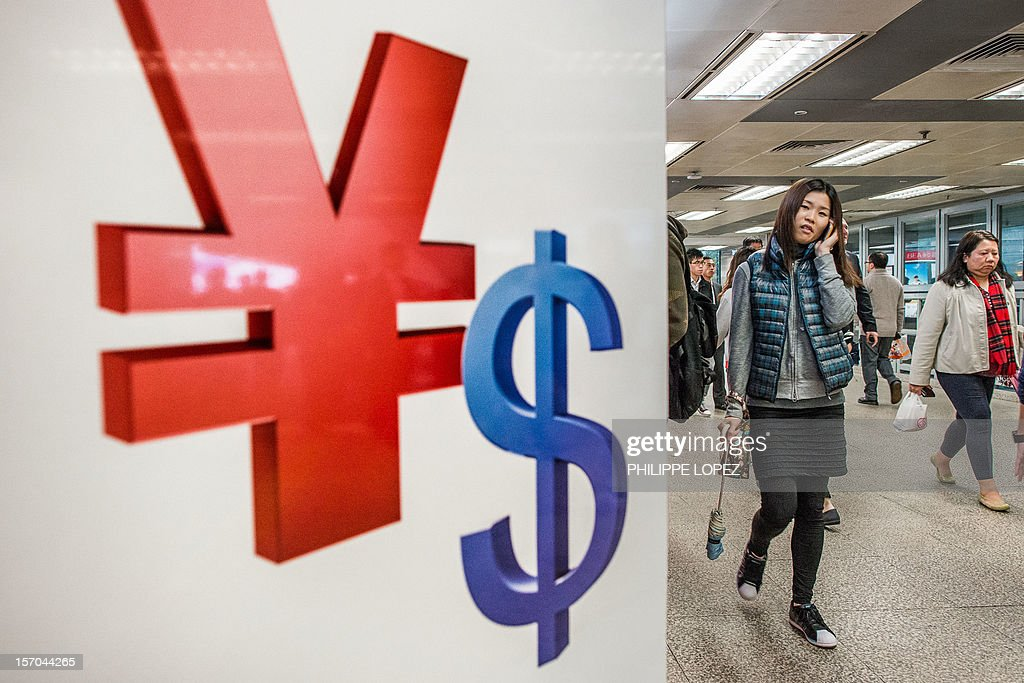 A woman walks past Chinese yuan (L) and US dollars symbols in Hong Kong on November 28, 2012. The US Treasury on November 27 again stopped short of labelling China a currency manipulator, noting gains in the value of the yuan, but said the currency remains 'significantly undervalued.' AFP PHOTO / Philippe Lopez
