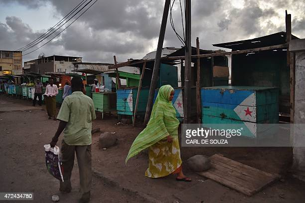 A woman walks past closed stalls selling khat painted with Djibouti's flag in Djibouti on May 3 2015 The herbal stimulant Khat also called miraa has...