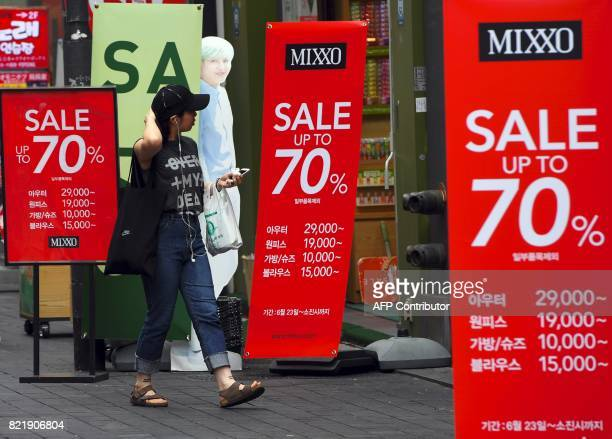 A woman walks past commercial signs advertising a sale at a shopping district in Seoul on July 25 2017 South Korea's economy is set to grow at its...