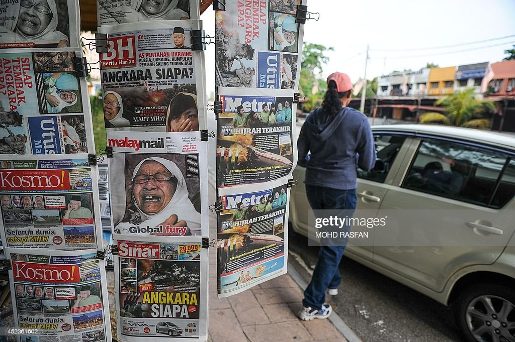 A woman walks past copies of Malaysian newspapers with reports about the Malaysia Airlines flight MH17 crashed in eastern Ukraine in Kuala Lumpur on July 19, 2014. Malaysia Airlines Flight MH17 carrying 298 people from Amsterdam to Kuala Lumpur crashed on July 17 in rebel-held east Ukraine, as Kiev said the jet was shot down in a 'terrorist' attack.