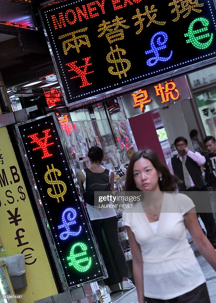 A woman walks past currency exchange signs in Hong Kong on September 15 2011 Hong Kong said it has no plans to unpeg its currency from the US dollar...