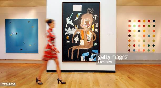 A woman walks past Damien Hirst's painting 'Blue Skies' JeanMichel Basquiat's painting 'The Thinker' and Hirst's 'Allodihydrocortisol' on October 10...