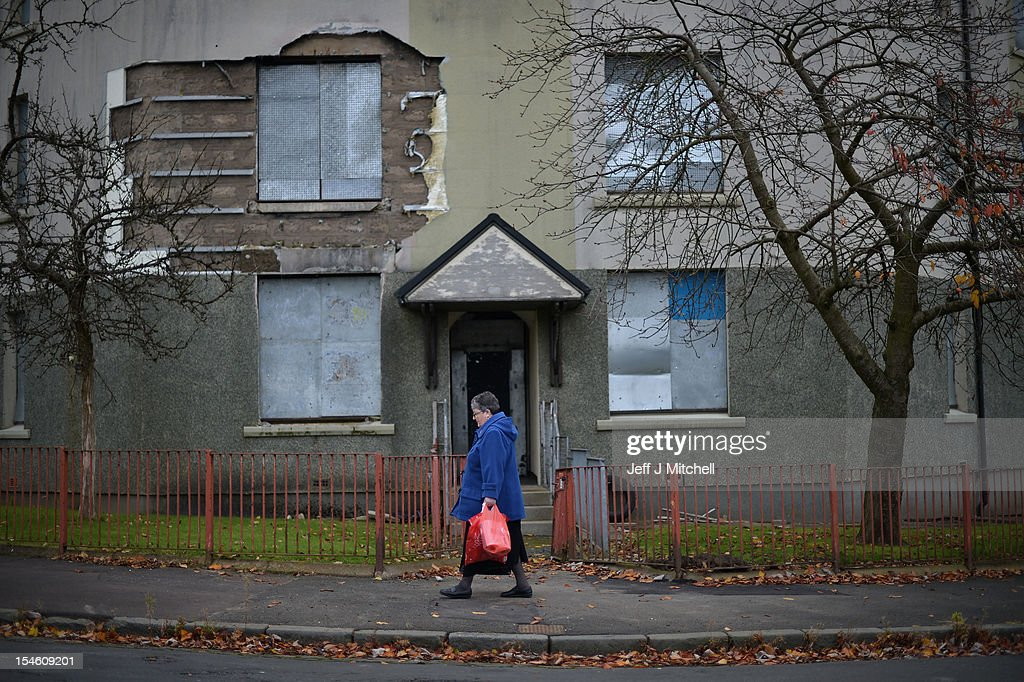 A woman walks past disused housing in the Hamiltonhill area on October 23, 2012 in Glasgow, Scotland. The Scottish National Party (SNP) have announced a welfare fund to provide emergency support to disadvantaged people who are struggling with issues such as unemployment, low income, poor health and lack of educational qualifications.