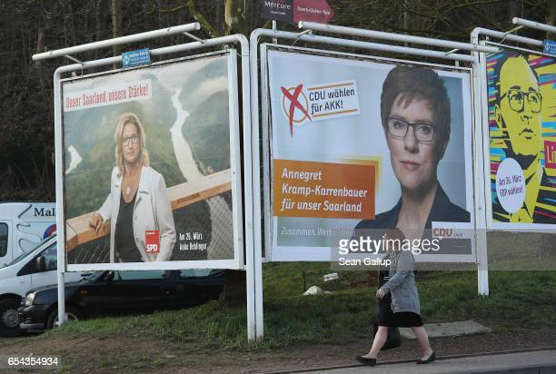 A woman walks past election campaign billboards on March 16 2017 in Saarbruecken Germany The billboard is sponsored by a group called Law and Freedom...