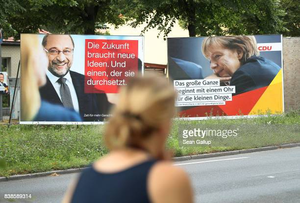 A woman walks past election campaign billboards that depict German Social Democrat and chancellor candidate Martin Schulz and German Chancellor and...