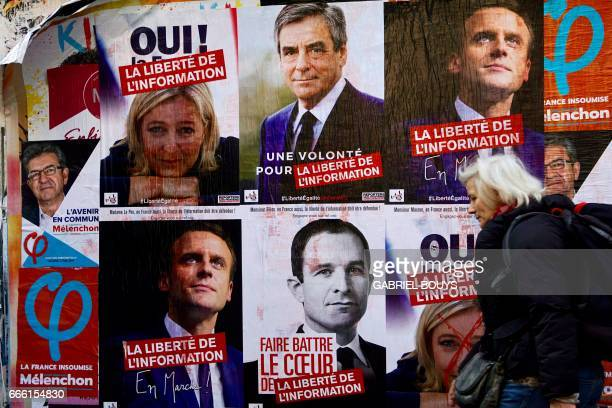 A woman walks past electoral posters of French presidential election candidate for the farleft coalition La France insoumise JeanLuc Melenchon French...
