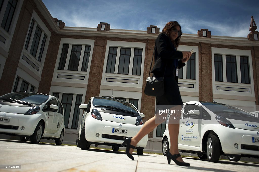 A woman walks past electric cars during the inauguration of the project 'Zem2All' at the Automobile museum in Malaga on April 25, 2013. Zem2All is a pilot project, carried out alongside the Japanese government, designed to estimate usage by drivers of electric vehicles in Malaga and provide an in-depth study of the impact of these vehicles.