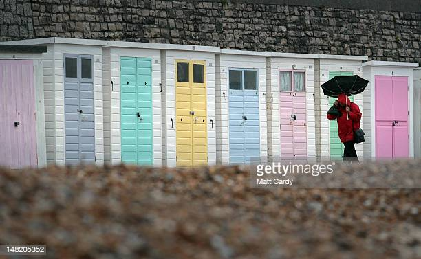 A woman walks past empty beach huts as people wait for the Olympic Flame to be carried around The Cobb as the Torch Relay passes through Dorset on...