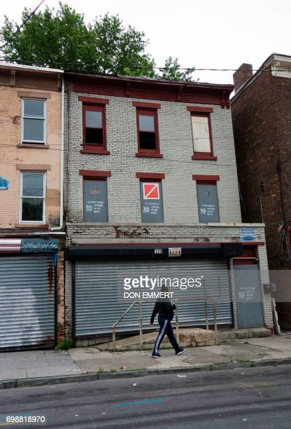 A woman walks past empty homes with gray boards on the doors and windows on May 30 in Newburgh New York Rows of boardedup homes became a ubiquitous...