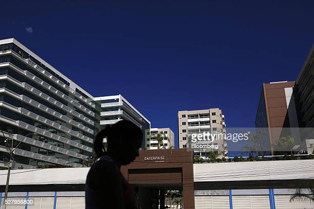 A woman walks past empty office buildings in Itaborai Brazil on Tuesday April 12 2016 Just 30 miles east of the bustling Copacabana beach Itaborai...