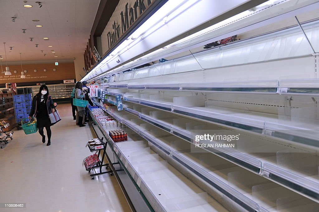 A woman (L) walks past empty shelves at a supermarket in the northwestern city of Akita on March 15, 2011 as panic buying sweeps the country following the March 11 earthquake and tsunami in eastern Japan as well as a nuclear crisis in Fukushima prefecture. Japan's nuclear crisis escalated on March 15 as two more blasts and a fire rocked the quake-stricken atomic power plant, sending radiation up to dangerous levels.